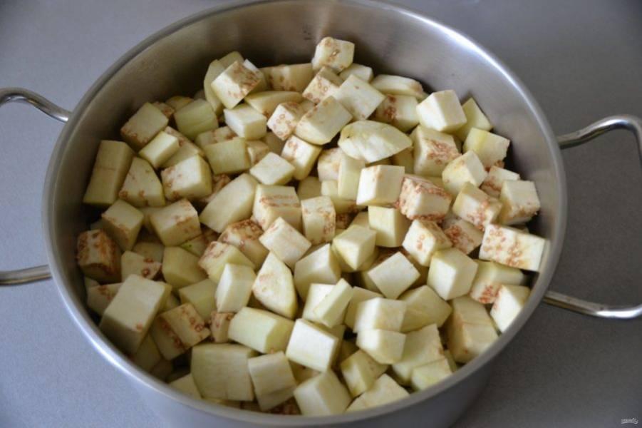 Помойте и очистите баклажаны от кожицы, нарежьте крупным кубиком, пересыпьте слоями солью, оставьте на 30 минут.