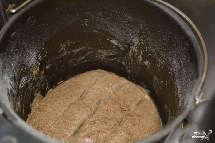 Отправляем нашу чашу в хлебопечь. Выполняем 1 замес в течение десяти минут, помогаем печке мешать массу силиконовой лопаточкой. 1 подъем занимает 20 мин. После выполняем второй замес: 5 минут и второй подъем (4 часа). Делаем после завершения 2 подъема ровные насечки на хлебе, чтобы он легко разламывался.