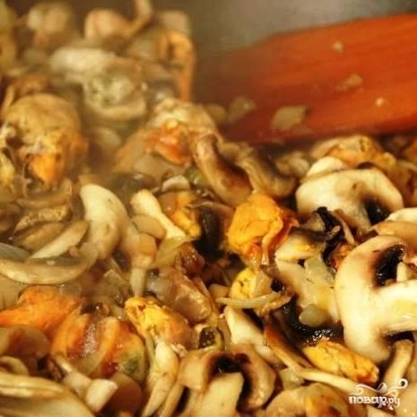 Следом отправляем в сковороду мидии, перемешиваем и обжариваем все вместе еще 3-4 минуты.