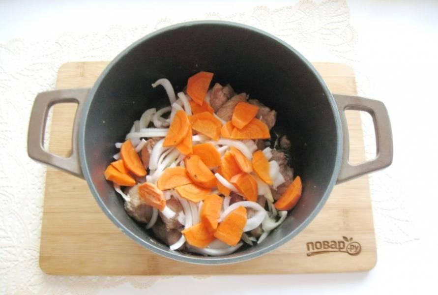 Морковь очистите, помойте и нарежьте произвольно. Добавьте в кастрюлю с мясом и луком. Налейте подсолнечное масло и тушите свинину с овощами перемешивая 10 минут.