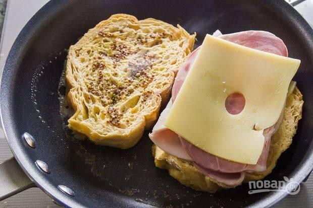 3. Сковороду поставьте на огонь, растопите в ней сливочное масло. Выложите 2 ломтика хлеба. Один посыпьте семенами горчицы, на другой выложите ветчину и сыр.