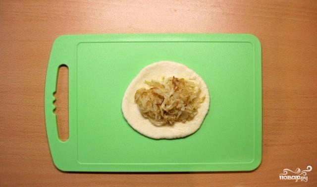 Приступаем к лепке пирожков: отделяем небольшой кусок теста и раскатываем его скалкой (можно просто размять руками, я обычно так и делаю). В середину кладем начинку из лука и капусты.