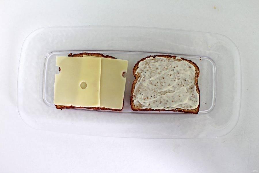 Один кусочек хлеба смажьте майонезом, а на второй положите сыр, нарезанный тонкими ломтиками.