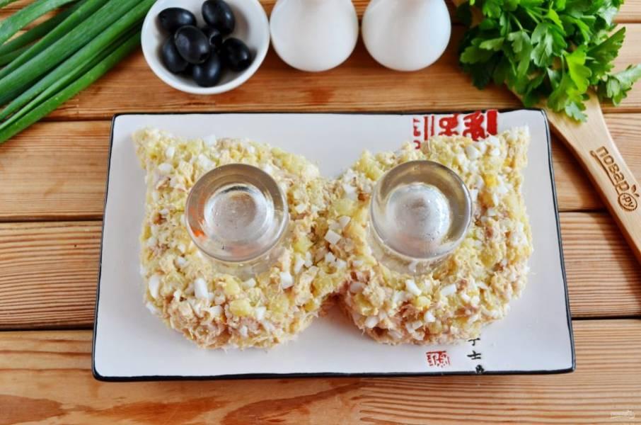 Возьмите удобную тарелку, поставьте две чистые рюмочки, вокруг выложите салат, формируя маску.