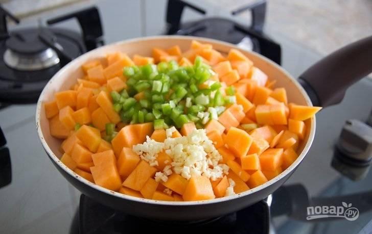 2. Выложите нарезанную кубиками мякоть тыквы, измельченный чеснок и чили. Аккуратно перемешайте и обжарьте на среднем огне, минутки 3.