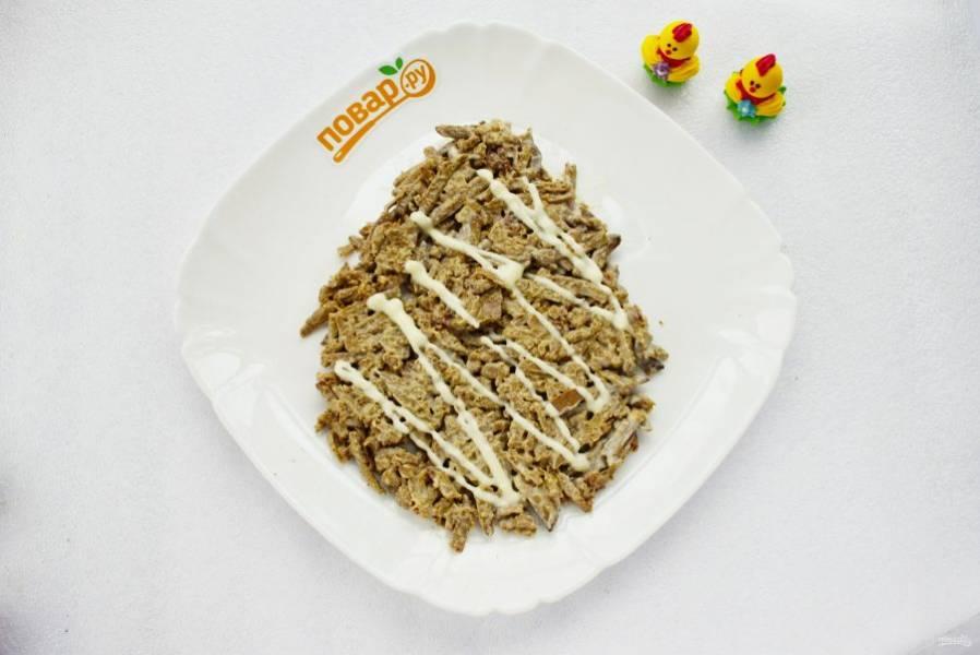 Начнем выкладывать салат слоями в форме яйца. Первый слой: натертую печень перемешайте с 2 ст. л. майонеза, разместите на блюде для подачи, сделайте сетку из майонеза.