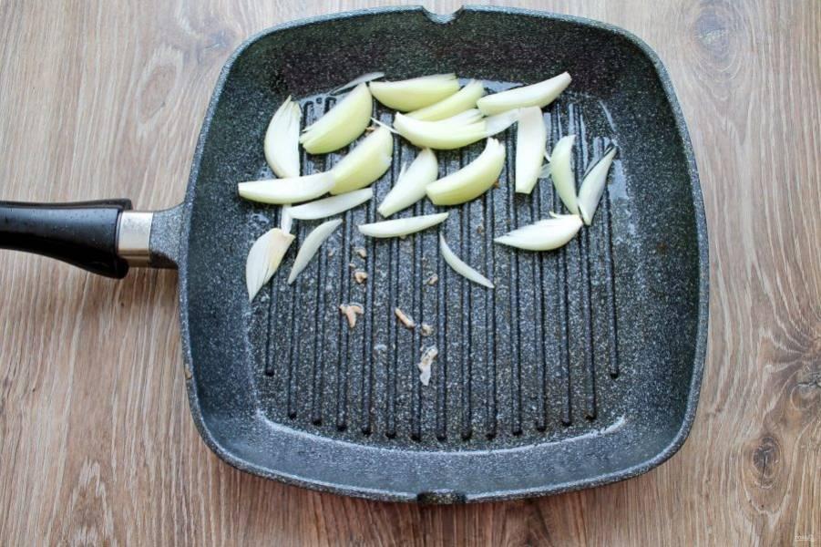 Репчатый лук почистите и порежьте дольками. Выложите его на половину сковороды в один слой.