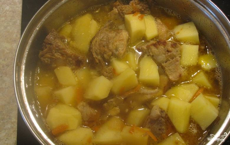 Картофель очищаем, нарезаем кубиками и складываем в кастрюлю к мясу. Доливаем воду так, чтобы покрыть картофель. Доведите блюдо до кипения, убавьте огонь, продолжайте тушить под крышкой еще 10-15 минут.