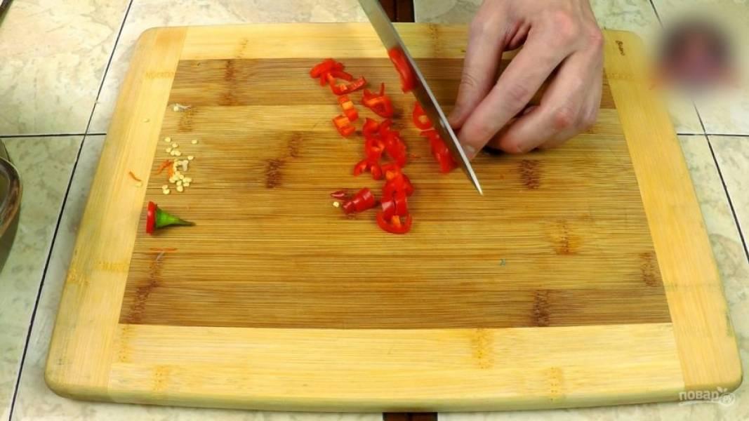 Удаляю из жгучего перца семена, режу его на дольки, также режу чеснок (не мелко).