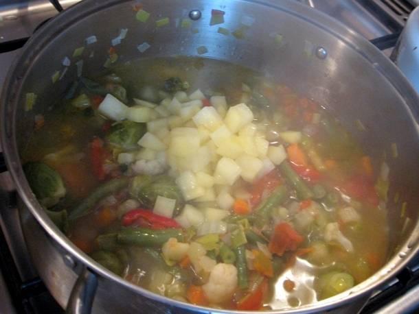 Далее выкладываем картофель и вливаем литр горячего овощного бульона (можно использовать воду, в которой варился картофель).