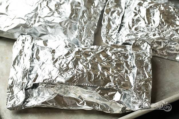 5.Плотно заверните фольгу, переложите рыбу на противень и отправьте в разогретый до 180 градусов духовой шкаф.