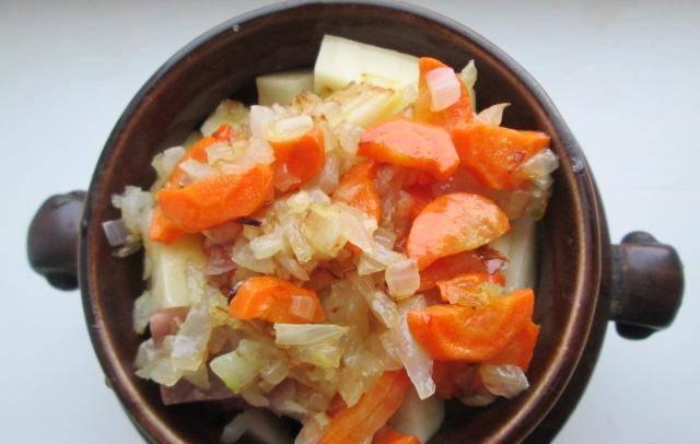 Сверху выкладываем обжаренный лук с морковью и поливаем сметаной. Накрываем горшочки крышкой и ставим в разогретую до 220 градусов духовку минут на 30-40 (до готовности картофеля).