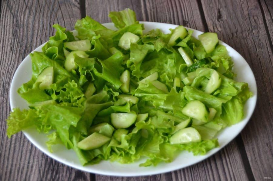 Руками нарвите листья салата, выложите на дно тарелки. Нарежьте огурцы дольками, уложите поверх салатных листьев.