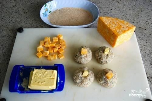 4. Влажными руками сформируйте небольшие котлетки. Нарежьте маленькими кубиками сыр и сливочное масло. Поместите в центр, утопив в фарше.