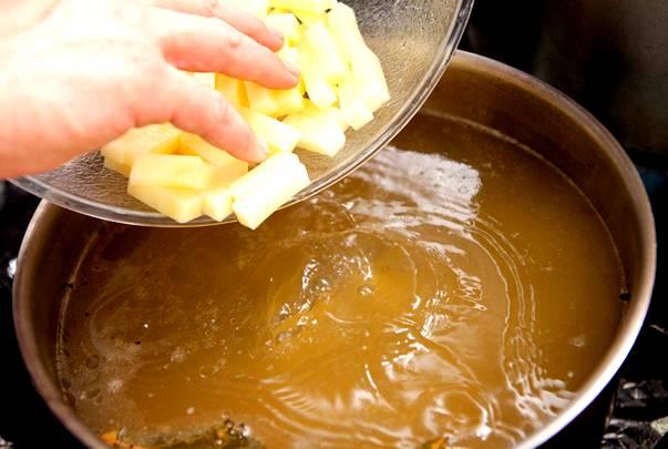 Пока овощи тушатся, вытаскиваем из сваренного бульона косточки и закладываем картошку. Также, можно положить перчик горошком, лавровый лист и специи.