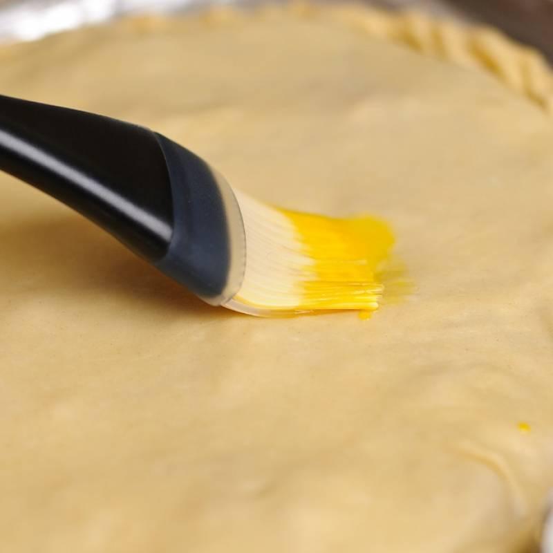 Закрываем начинку второй частью теста, запечатываем края. Смешиваем яйцо с небольшим количеством воды и промазываем кисточкой верхнюю часть пирога. Сделайте небольшие надрезы.