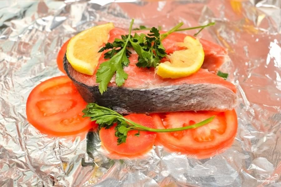 На фольгу выложите сначала ломтики помидора. Затем стейк лосося. Посолите его и поперчите. Добавьте, если хотите, любимых приправ. На стейк аккуратно положите ломтики лимона и веточки петрушки.