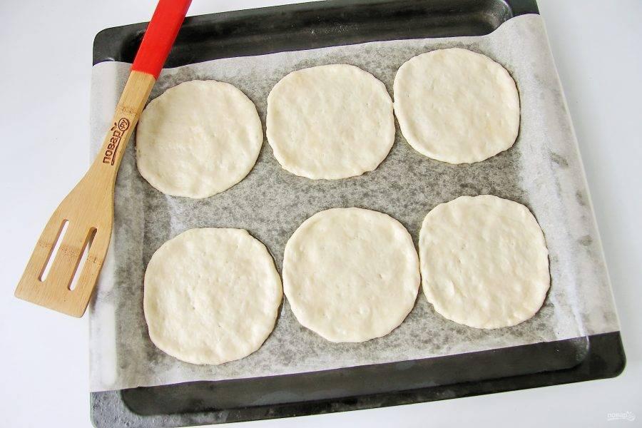 Смажьте руки растительным маслом, сформируйте из теста шарики, переложите их на противень и расплющите руками в лепешку. Противень предварительно застелите пергаментом и смажьте маслом.