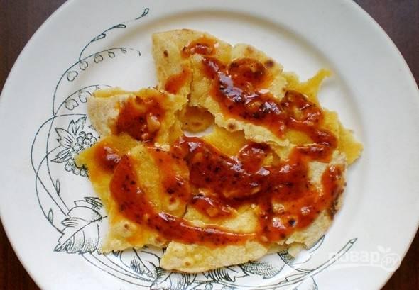 Томите соус на сковороде, помешивая, пару минут. Потом нарвите питу руками. Уложите её на тарелку для подачи и полейте соусом.