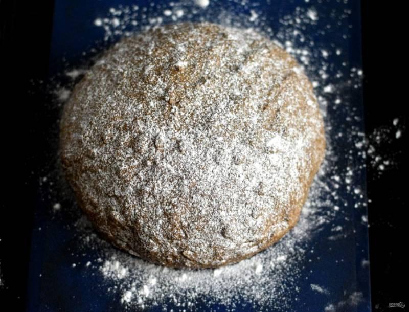 Переложите хлеб на лист с пергаментом или ковриком и притрусите его сверху мукой. Дайте еще немного подойти.