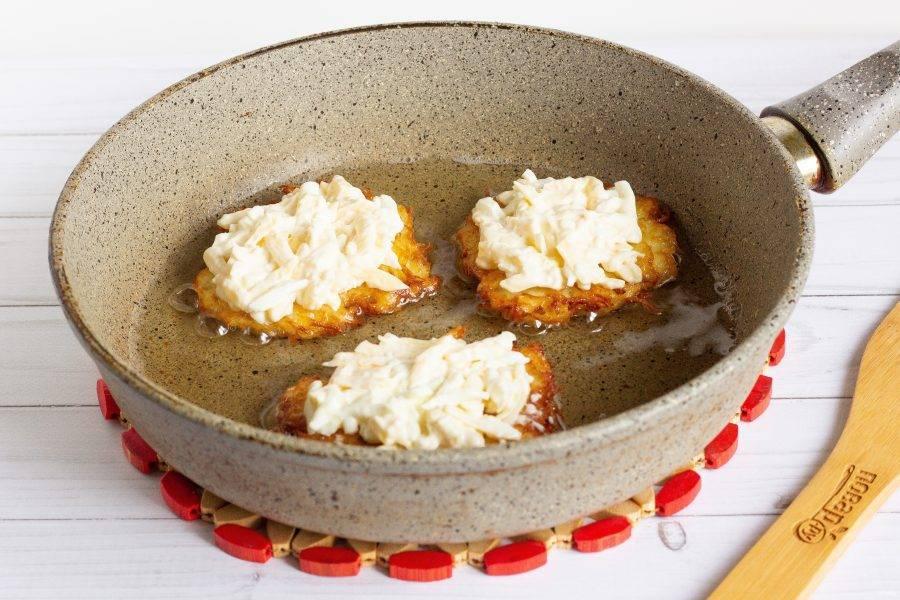Затем переверните, поджарьте 1-2 минуты и выложите на каждый драник сырную массу. Накройте крышкой и жарьте ещё 1-2 минуты, чтобы сыр расправился.