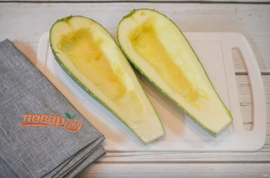 5. Кабачок разрежьте вдоль пополам, удалите семена. Смажьте маслом, присыпьте чесноком.