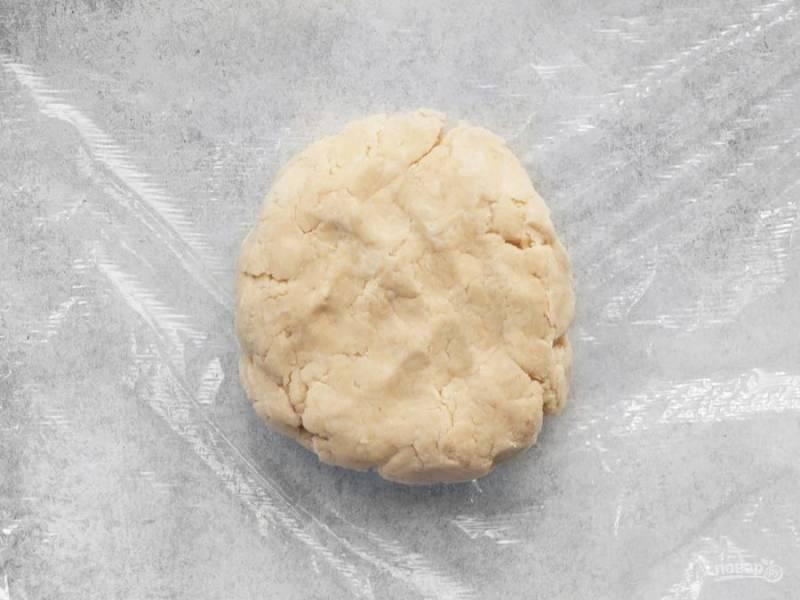 3.Вливайте в мучную крошку по столовой ложке холодной воды, затем соберите тесто в единый ком и оберните его в пленку. Отправьте тесто на 1 час в холодильник.