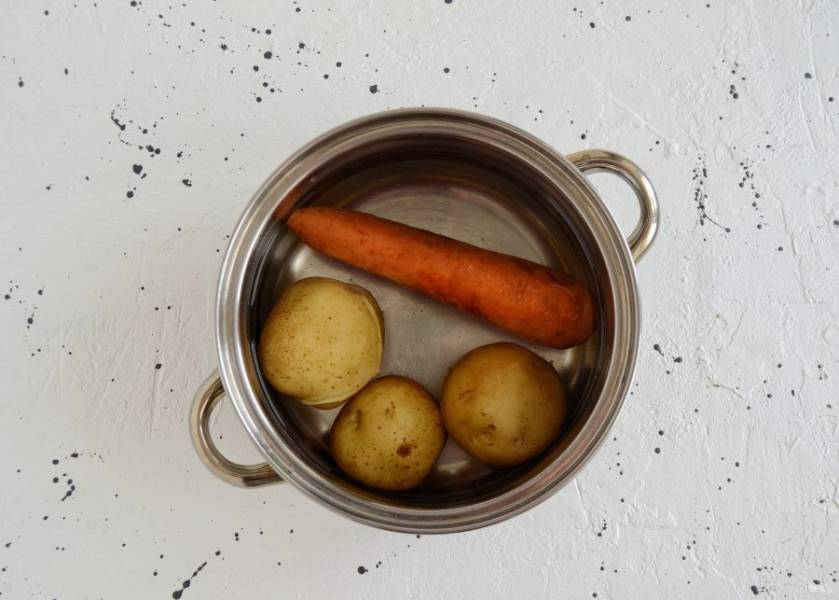 Отварите в кипящей воде картошку и морковь. Затем остудите.