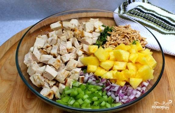 Подготовьте ингридиенты для салата. Мякоть ананаса нарежьте кубиками. Жареную куриную грудку нарежьте небольшими кусочками. Миндаль слегка обжарьте на сковородке. Выложите все в глубокую миску. Добавьте нарезанный красный лук, сельдерей,  петрушку и уже поджаренный миндаль.