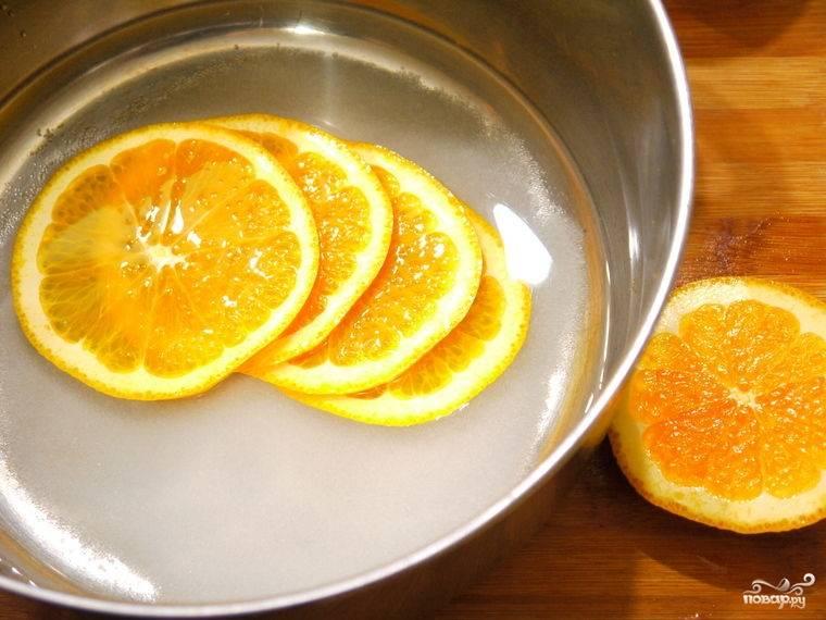 Сахар, воду и нарезанный дольками апельсин кладем в кастрюльку и ставим на медленный огонь. Варим около 20 минут на слабом огне, пока не выпарится 2\3 жидкости.