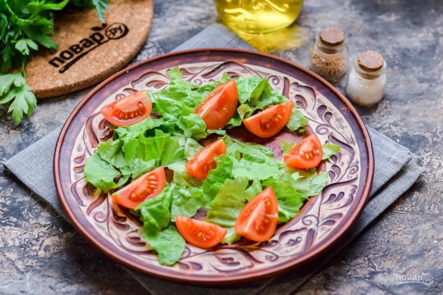 Салатные листья ополосните и просушите, порвите руками и выложите на тарелку. Черри нарежьте дольками и выложите в салат.