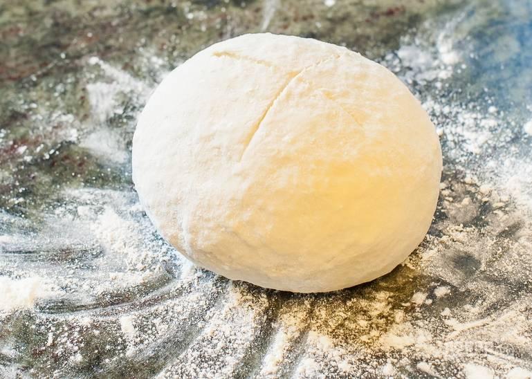 """Приготовим тесто. В глубокую емкость вливаем теплую воду и растворяем в ней дрожжи. Засыпаем соль и сахар и вливаем оливковое масло. Тщательно перемешиваем до полного растворения. Подсыпая просеянную муку, замешиваем тесто, чтобы не прилипало к рукам. Скатайте тесто в шар, накройте его полотенцем и дайте ему """"отдохнуть"""" один час."""