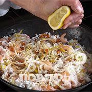 Выложить рис и креветки в сковороду. Добавить изюм и приправить соевым соусом, кунжутным маслом и соком 1/2 лимона. Посыпать укропом, обжаривать до готовности.