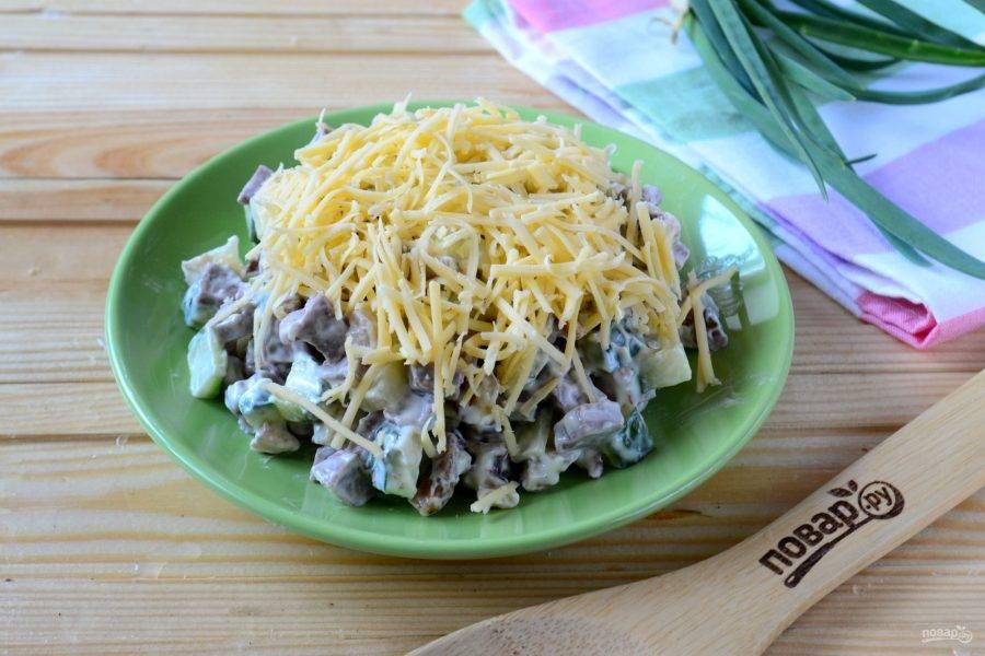 Выложите салат на плоскую тарелку горкой. Сверху присыпьте натертым на мелкой терке сыром. Салат готов, кушайте с удовольствием!