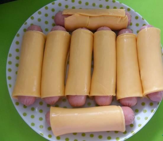 1. Сосиски освобождаем от оберток. Каждую сосиску заворачиваем в кусочек сыра.