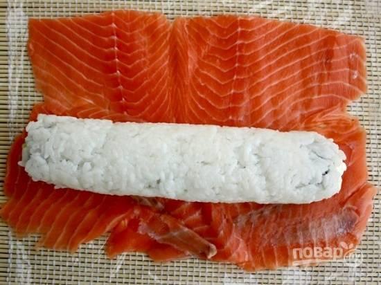 Нарежьте острым ножом рыбу на тонкие ломтики и разместите их на коврике сплошным слоем, без просветов. Выложим рисовый ролл на рыбу.
