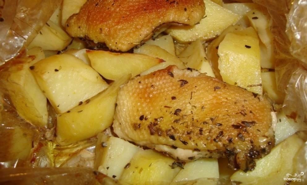 2. Теперь складываем в пакет для запекания картошку и лук, посыпаем их солью и специями. Наверх - кусочки утки. Сбрызнем картошку маслом, завяжем края пакета и отправим на час в духовку запекаться при 180 градусах.
