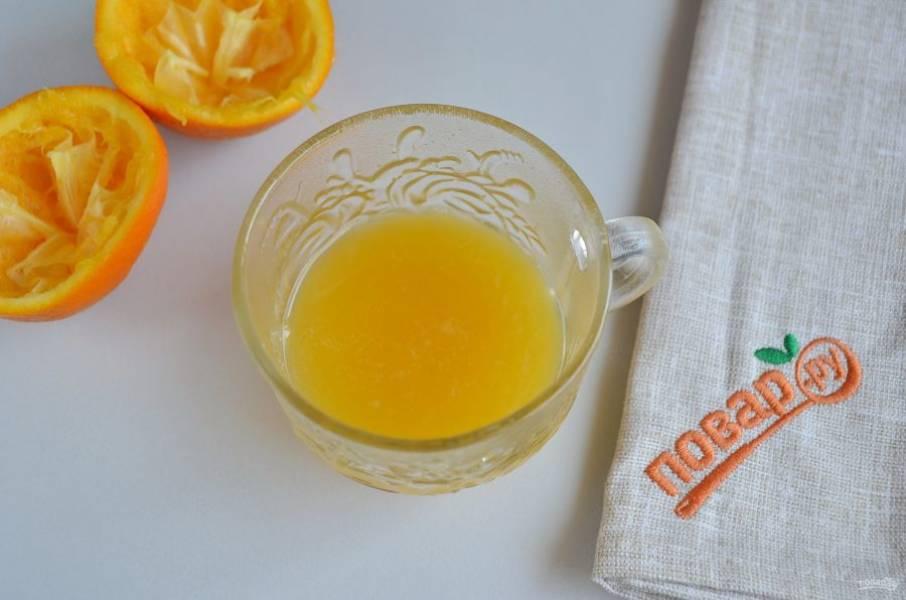 2. Вымойте апельсин, порежьте на две половинки и отожмите сок. Процедите от косточек.