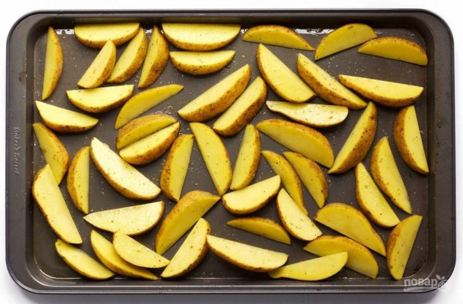 3. Картофель помойте и нарежьте дольками, затем выложите на противень, сбрызните оливковым маслом, посыпьте чесночным порошком и оставшимся сушеным орегано, посолите и поперчите.