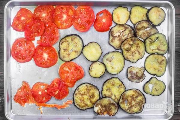 1.Вымойте баклажаны и нарежьте кружочками, толщиной 1 сантиметр, выложите на поднос и посыпьте солью, оставьте на 30 минут, затем промокните салфетками. Нарежьте томаты кружочками. Выложите овощи на противень, полейте оливковым маслом, посолите и поперчите. Запекайте овощи в разогретом до 220 градусов духовом шкафу 15 минут.