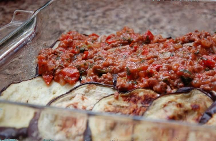 Выложите в форму слой баклажан затем слой фарша с соусом.