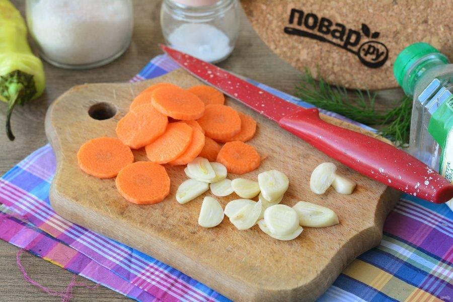 Почистите чеснок и морковку. Нарежьте овощи пластинками и кружочками. Если кружочки крупные, то поделите их пополам.