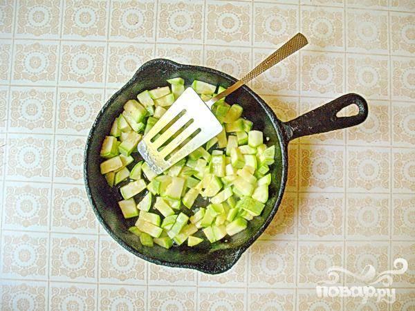 4.Теперь надо вымыть кабачок и нарезаем большими кусочками.  В другую сковороду вливаем масло, разогреваем, добавляем кабачки, и на маленьком огне с закрытой крышкой тушим минут 5. Все время помешиваем.