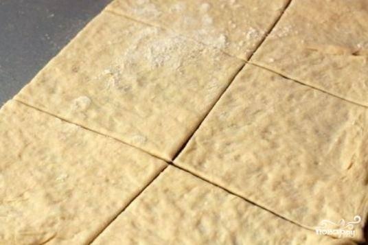 Слоеное тесто разморозим и раскатаем на щедро посыпанной мукой поверхности. Нарежем его на 12 прямоугольников.