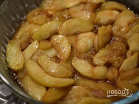 Форму для пирога, диаметром в 24 см, смазываем маслом и выкладываем яблоки в карамели.