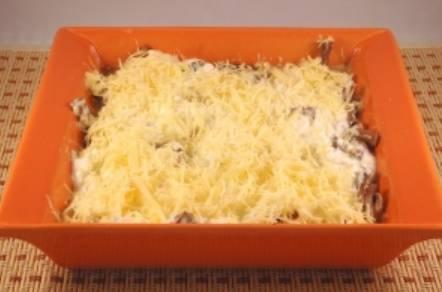 Извлекаем грибы из духовки, обильно смазываем их сметанным кремом. Посыпаем оставшимся сыром.
