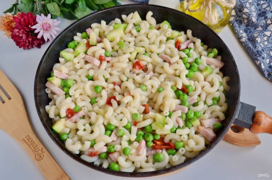 К овощам и ветчине добавьте готовые макароны, влейте 50 мл воды (в которой они варились) и прогрейте все, перемешайте. Снимите с огня и добавьте оставшееся оливковое масло.
