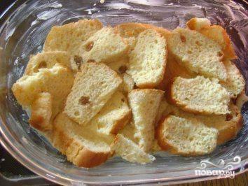 Форму для выпечки смажьте сливочным маслом. Черствые булочки или батон нарежьте ломтиками. Выложите половину на дно формы.