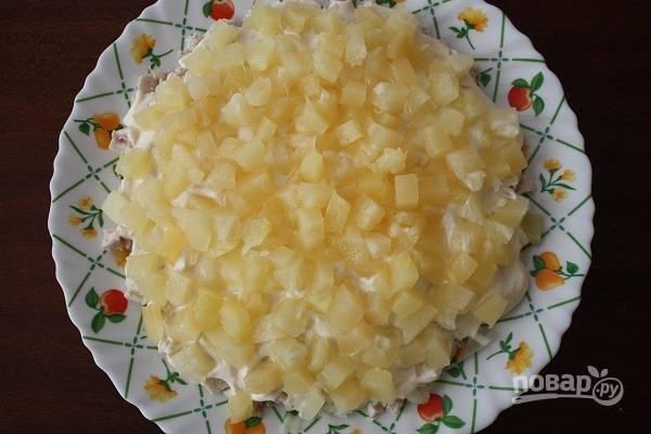 4. Нарежьте ананас кубиками (если он у вас изначально кольцами), распределите его ровным слоем.