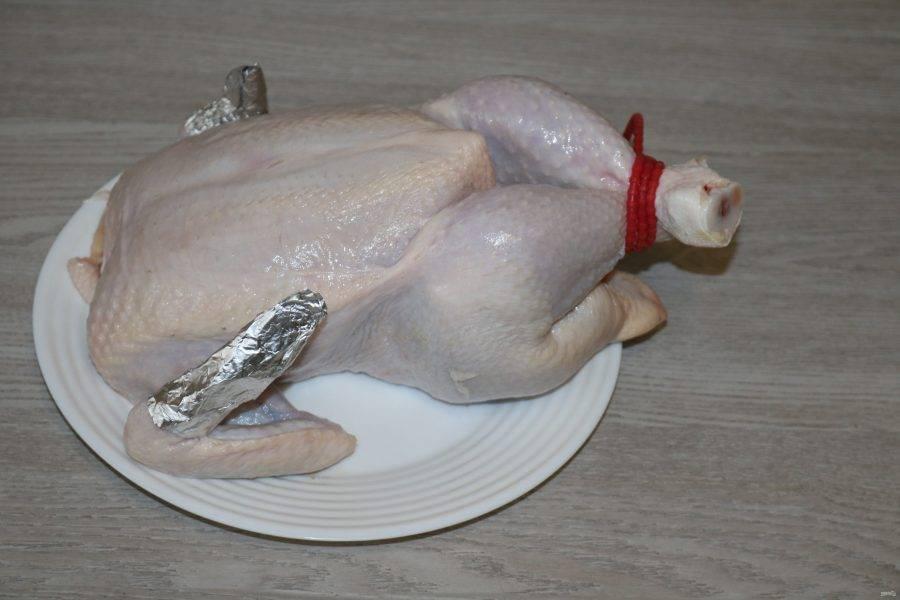 Курицу промойте, обсушите бумажным полотенцем. Ножки свяжите, на крылышки оденьте по небольшому кусочку фольги.